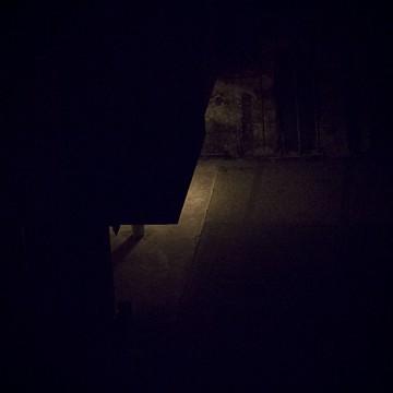 Plano general cenital, color. Portal de calle oscura iluminado por solo una luz escondida.