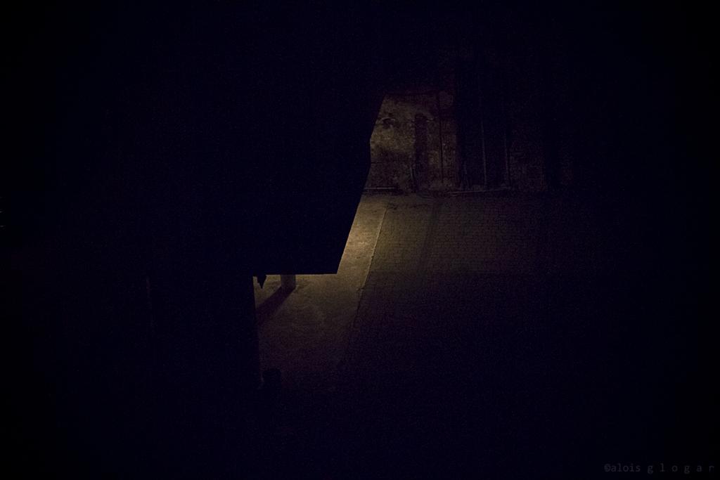 Primer post. Plano general cenital, color. Portal de calle oscura iluminado por solo una luz escondida.