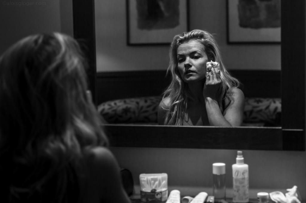 Estilo fotográfico. Plano general, blanco en negro. Modelo retocando maquillaje en descanso de una sesión.