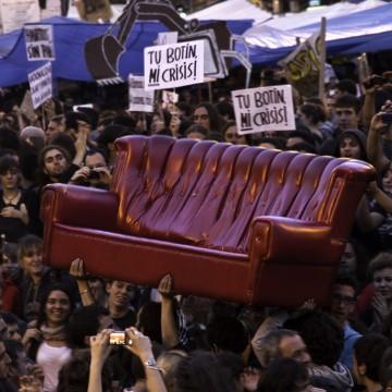 Plano general, color. Manifestantes del 15M en Plaza Sol (Madrid) llevando en volandas un sofá rojo.