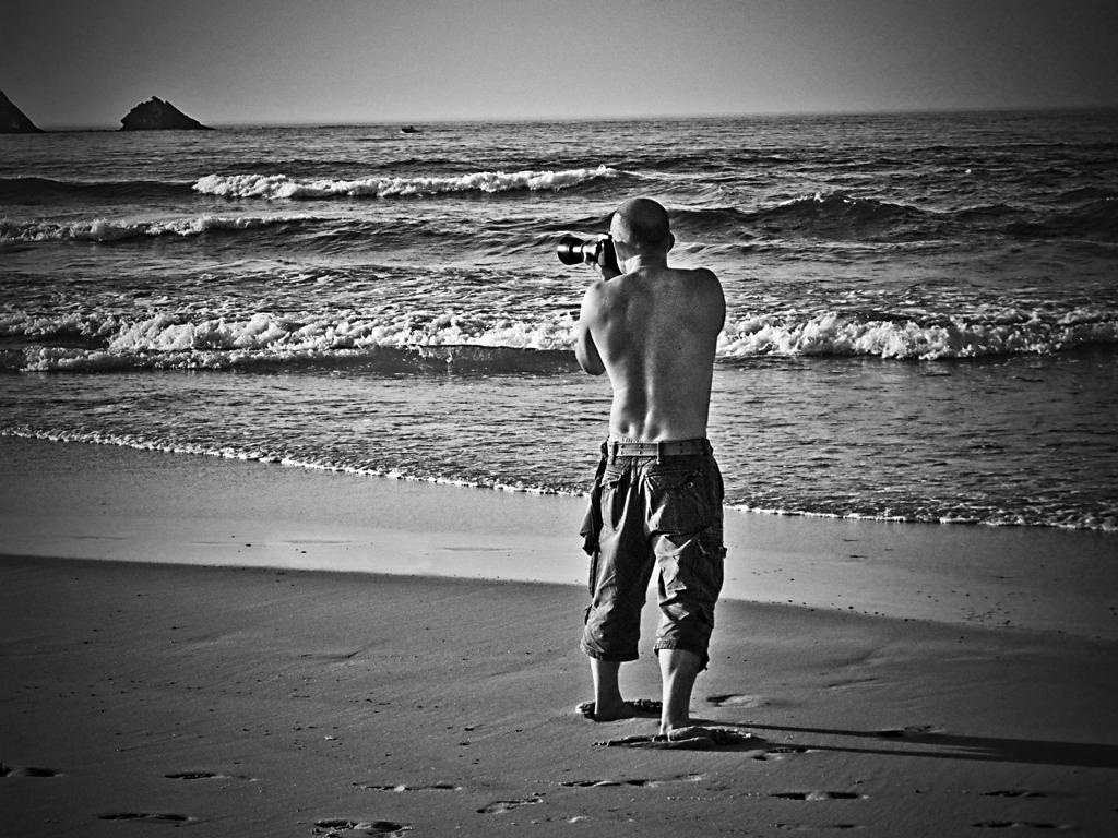 Plano general, blanco y negro. Tomando fotografías, de espaldas, en la playa y sin camiseta.