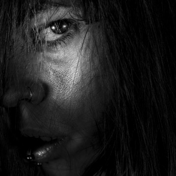 Primer primer plano, blanco y negro. Todo en sombras excepto el ojo de la modelo que mira amenazante a cámara.