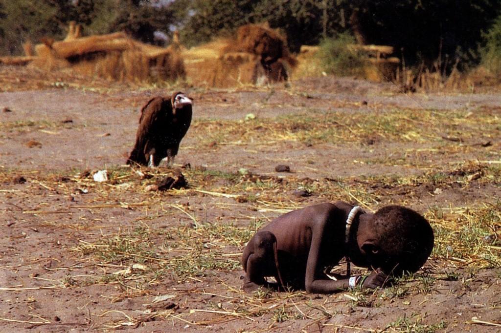Fotografías polémicas. Plano general, color. Niño africano esqueletico encogido sobre si mismo. Un buitre le observa al fondo.