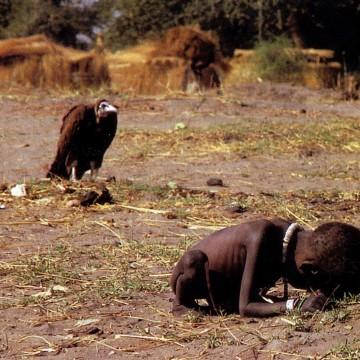 Plano general, color. Niño africano esqueletico encogido sobre si mismo. Un buitre le observa al fondo.