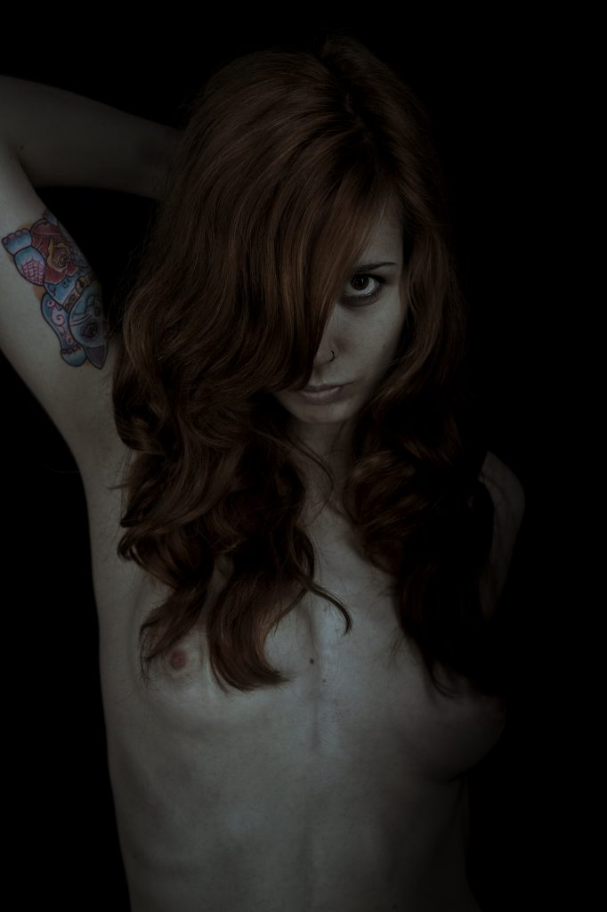 proyecto autobiografía. Plano medio, color. Modelo con brazo levantado y pelo tapándole media cara y mirando a cámara.