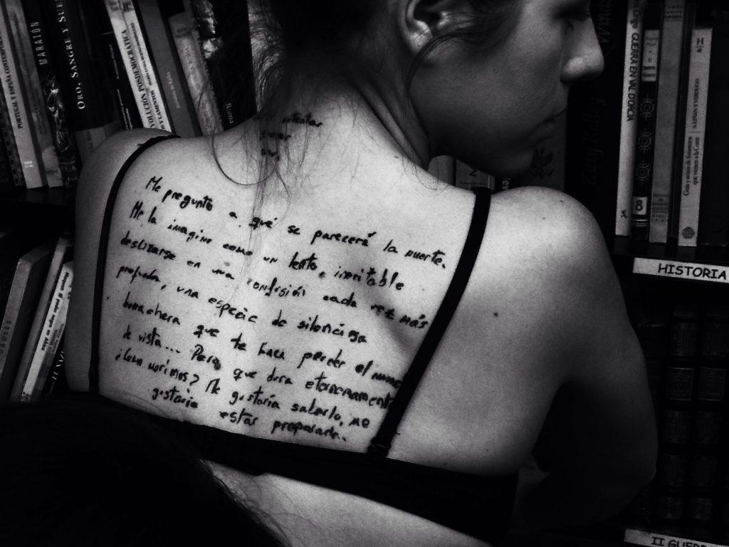 ¿Hace falta saber escribir para ser fotógrafo? Plano medio, blanco y negro. Modelo de espaldas, con un texto tatuado en la espalda.