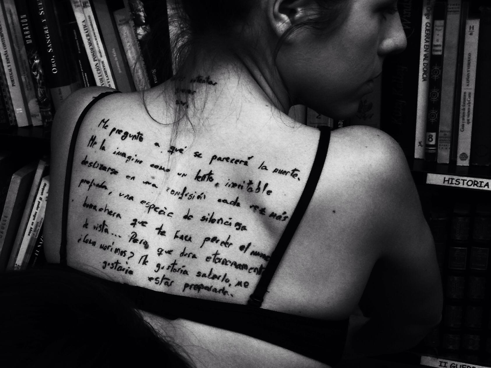 Plano medio, blanco y negro. Modelo de espaldas, con un texto tatuado en la espalda.