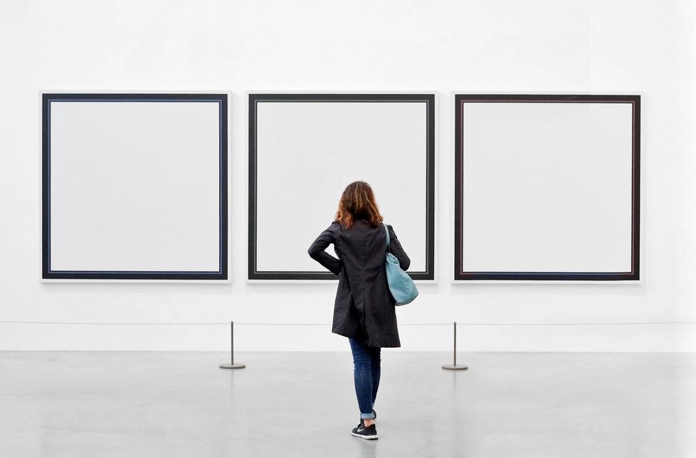 Plano general, color. Mujer mirando cuadros vacíos en un museo.