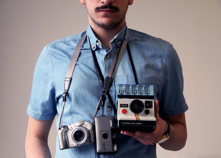 Plano medio, color. Fotógrafo con varias cámaras colgadas del cuello.