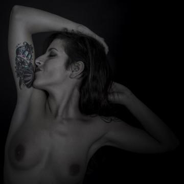 plano medio, color. Modelo, desnuda y tatuada, besándose el tatuaje del brazo.
