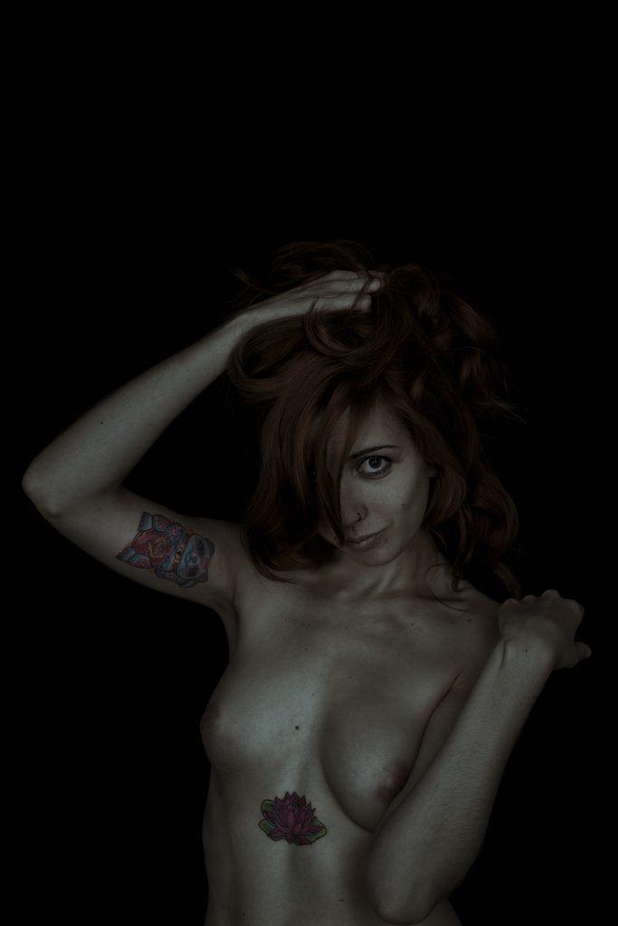 Plano medio, colo. Modelo, desnuda y tatuada, recogiéndose el pelo y mirando a cámara