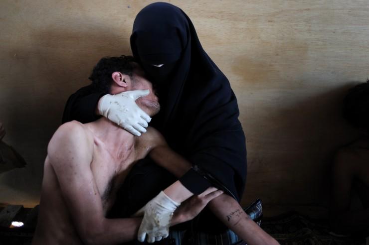 """Plano medio, color. Madre sujetando a su hijo herido de bala. Composición que recuerda a """"La pietá"""" de Miguel Angel."""