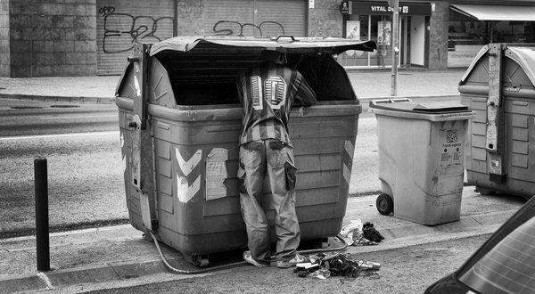 Plano general, blanco y negro. Mendigo buscando comida en un contenedor en España durante la crisis del 2008