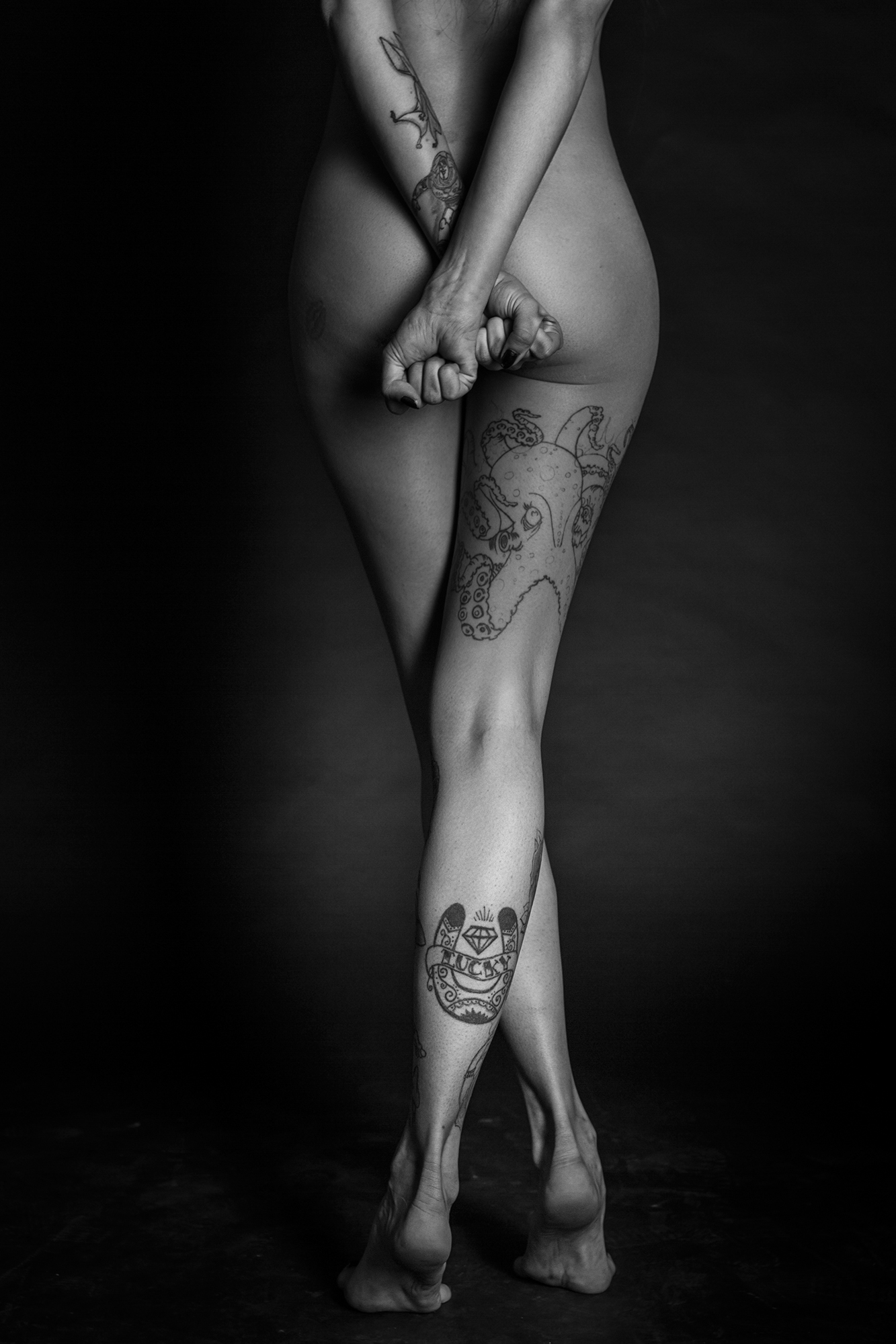 Plano medio, blanco y negro. PIernas y culo de modelo, vista de espaldas. Piernas cruzadas y puños, sobre el culo, apretados.
