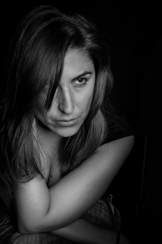 Plano medio, blanco y negro. Laura Lobo, reportera y presentadora de televisión, con el codo apoyado en la rodilla y actitud pensativa.