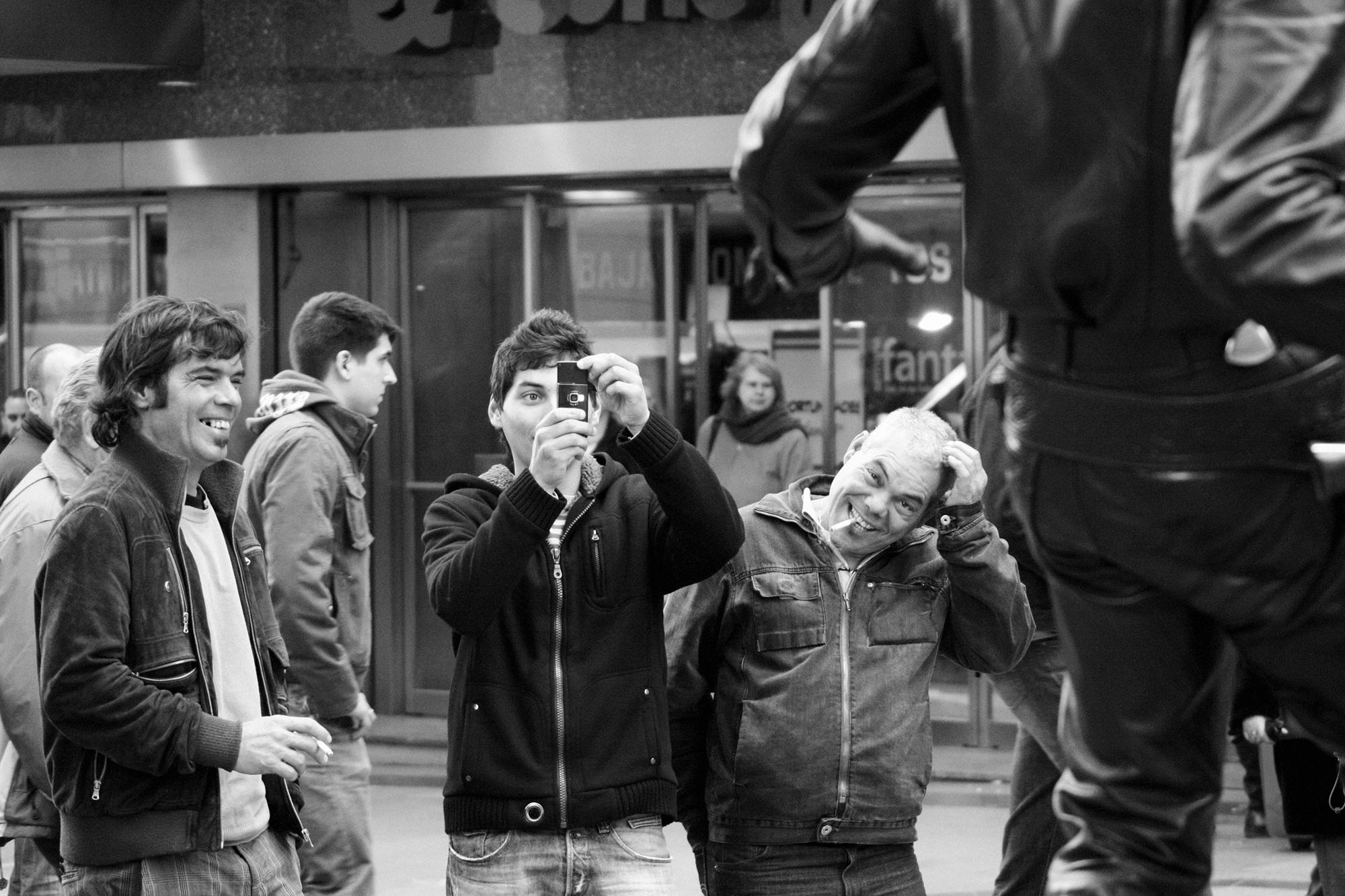 plano general, blanco y negro. grupo de gente haciendo fotos, en actitud burlona, a una estatua viviente en la calle.