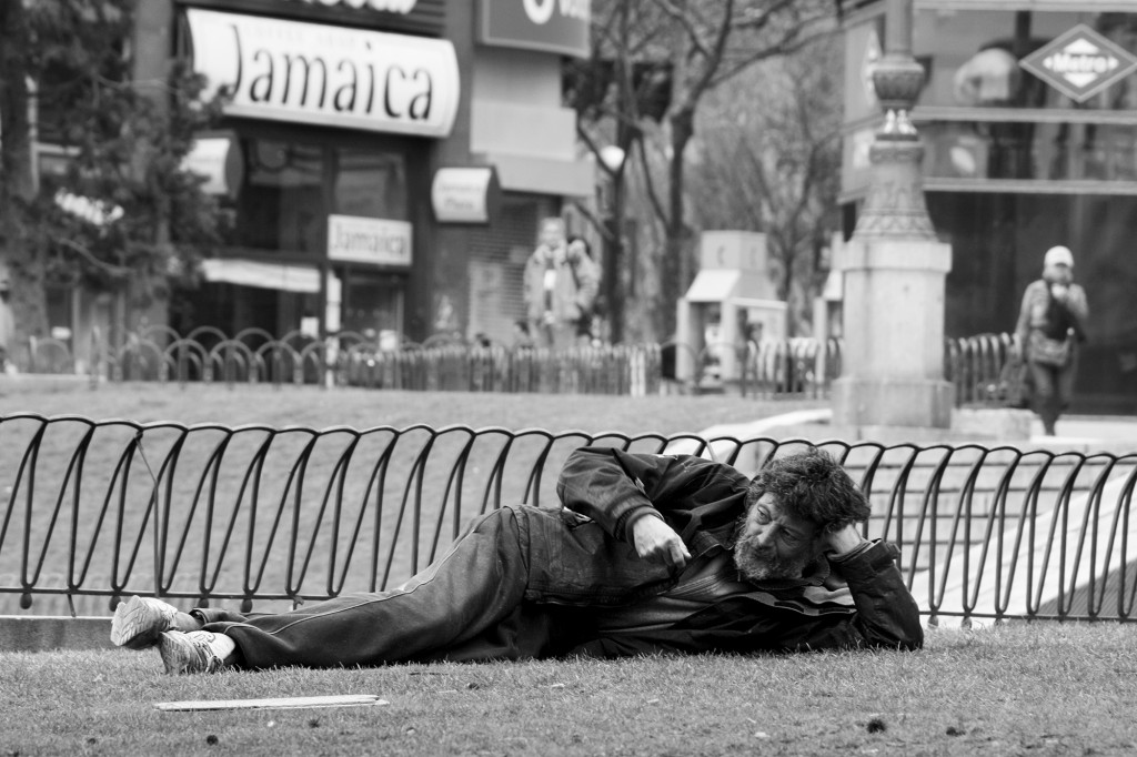 """¿Los reportajes fotográficos cuentan la verdad? Plano general, blanco y negro. Mendigo tumbado en un parque. De fondo el cartel de un bar que se llama. """"Jamaica"""""""