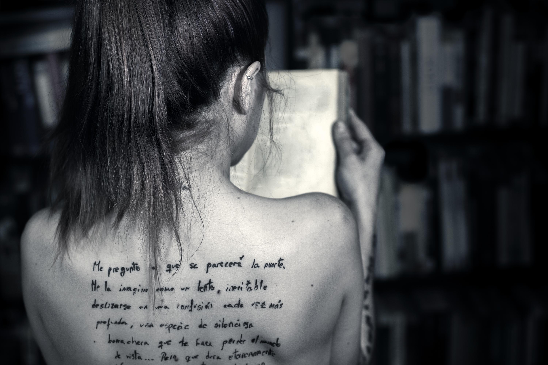Plano medio, blanco y negro. Modelo con texto tatuado en la espalda leyendo un libro con librería de fondo.
