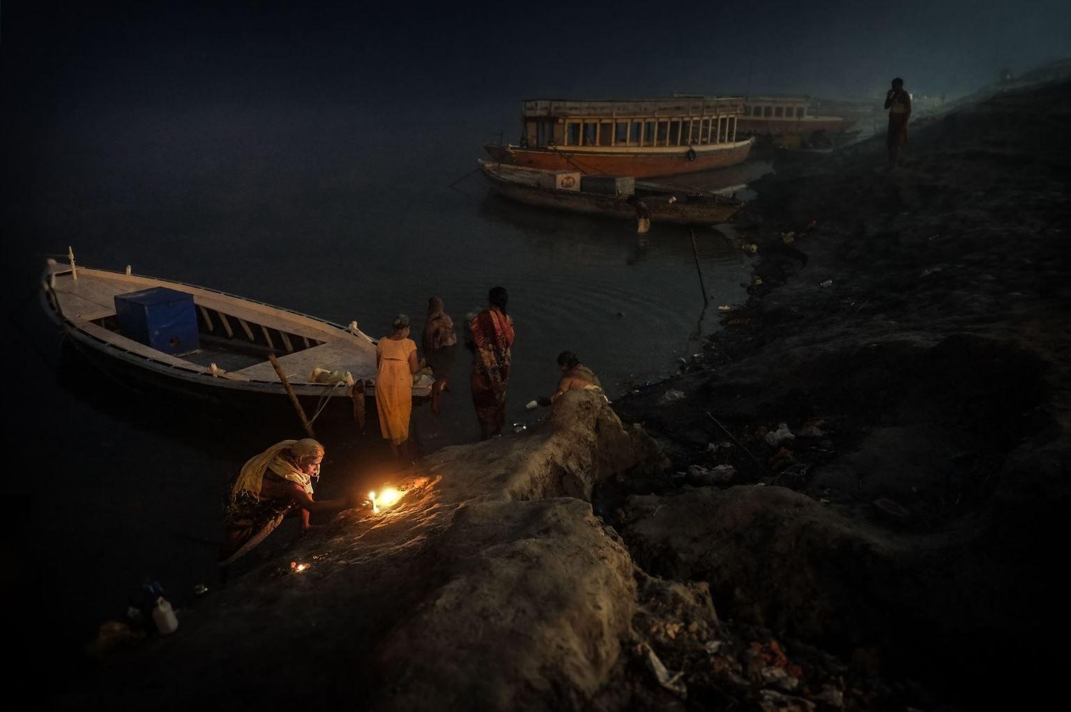 Plano general, color. Hindus preparando los rezos a la orilla del Ganges.