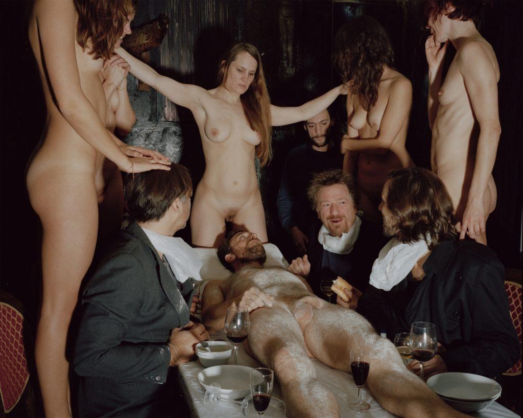 Plano general, color. Recreación de cuadro autopsia transformado en cena sobre cuerpo de hombre desnudo con parejas desnudas y vestidas alrededor.