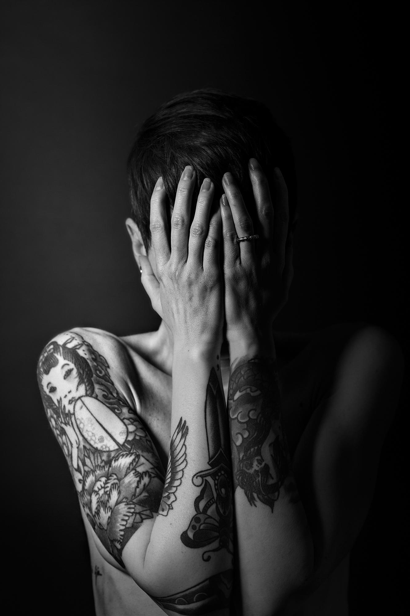 Plano medio, blanco y negro. Modelo tatuada posando desnuda con las manos tapándose la cara.