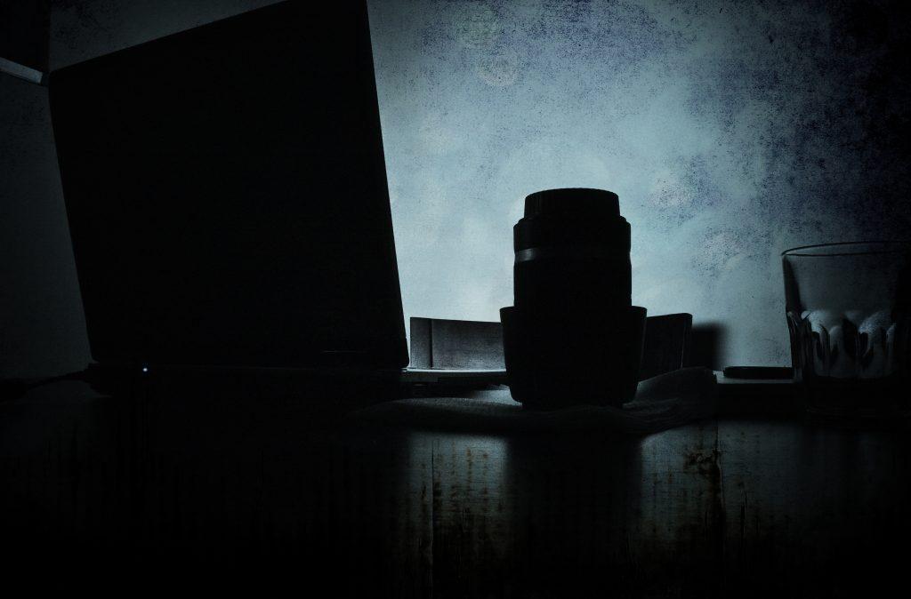 10 links fotográficos imprescindibles. Plano general, color. Contraluz de un portátil y un objetivo sobre una mesa con fondo azul.