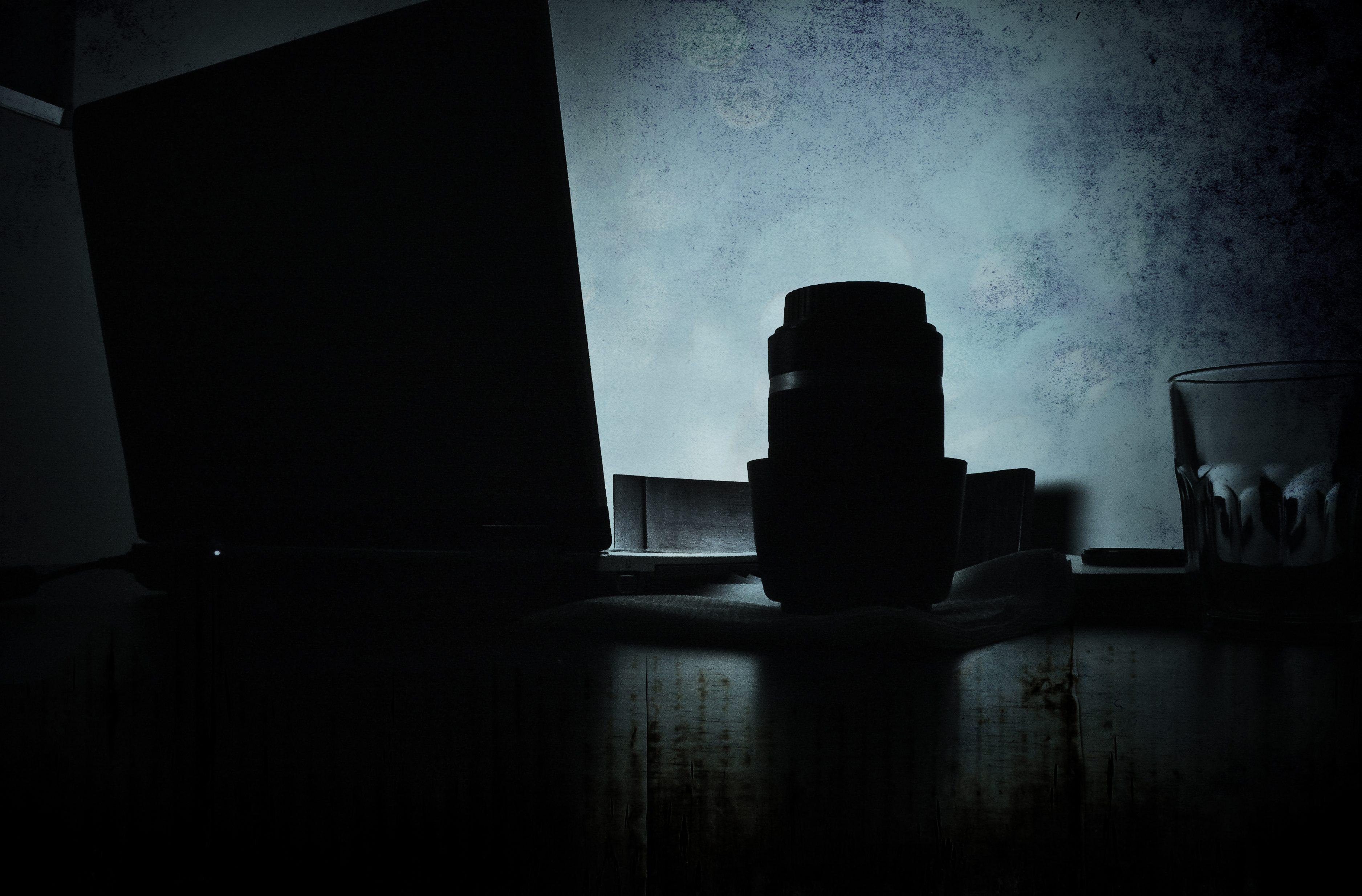 Plano general, color. Contraluz de un portátil y un objetivo sobre una mesa con fondo azul.