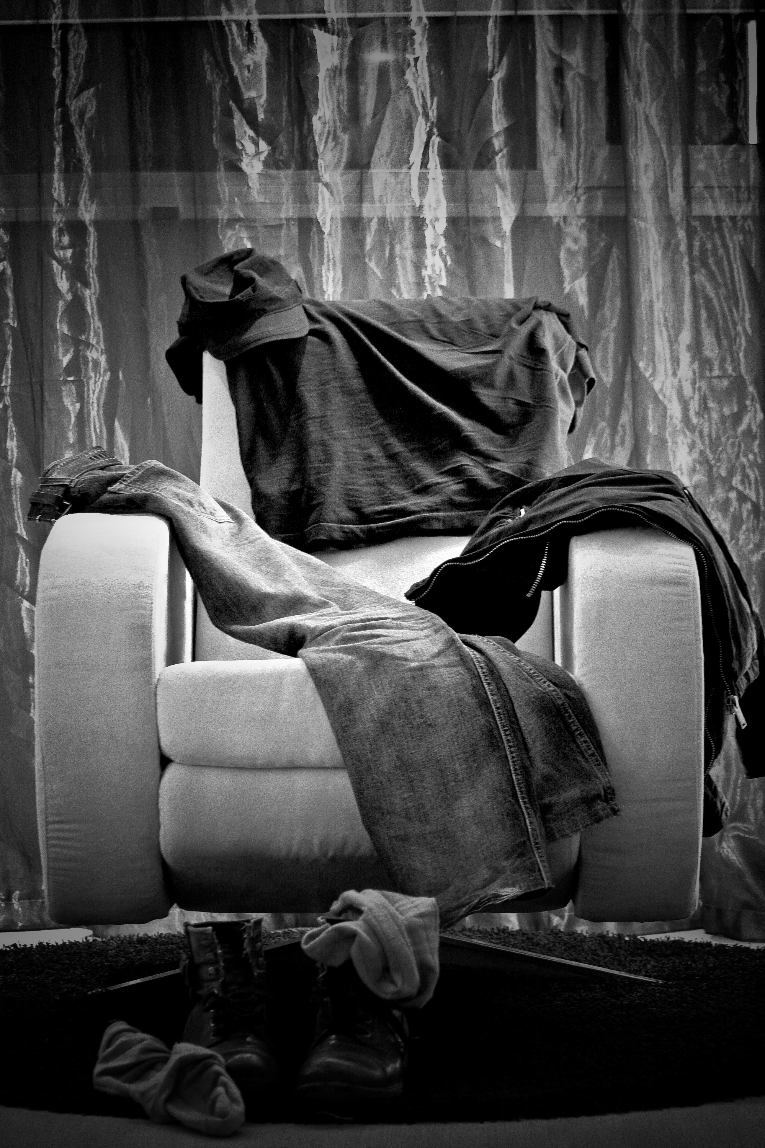 Plano general, blanco y negro. Ropa dejada sobre sillón de habitación de hotel con fondo de cortinas
