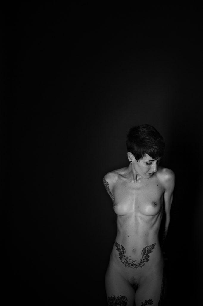Plano americano, blanco y negro. Modelo tatuada posando desnuda con la manos en la espalda