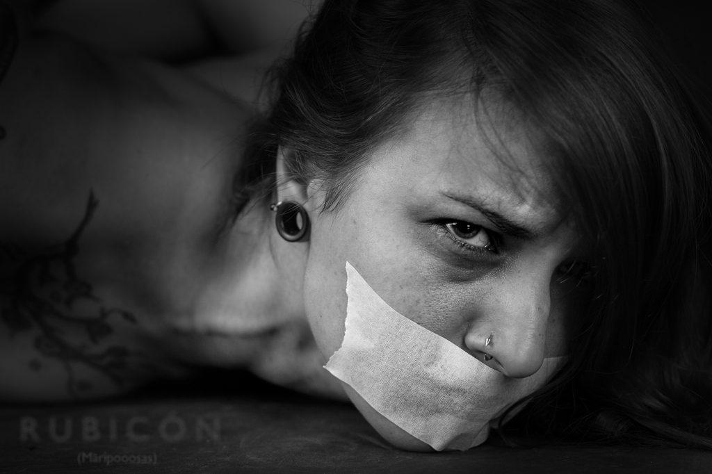 Primer plano, blanco y negro. Modelo acostada en el suelo, con expresión de terror y cinta adhesiva tapándole la boca.