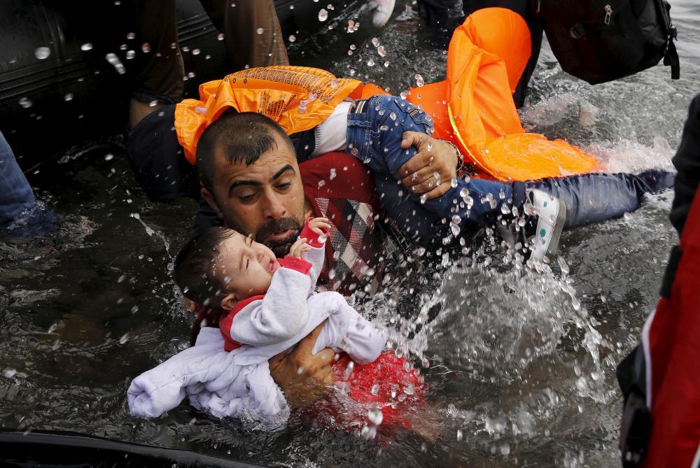 Plano general, color. Refugiado salta de la lancha a la playa con hijo en brazos luchando por no ahogarse los dos.