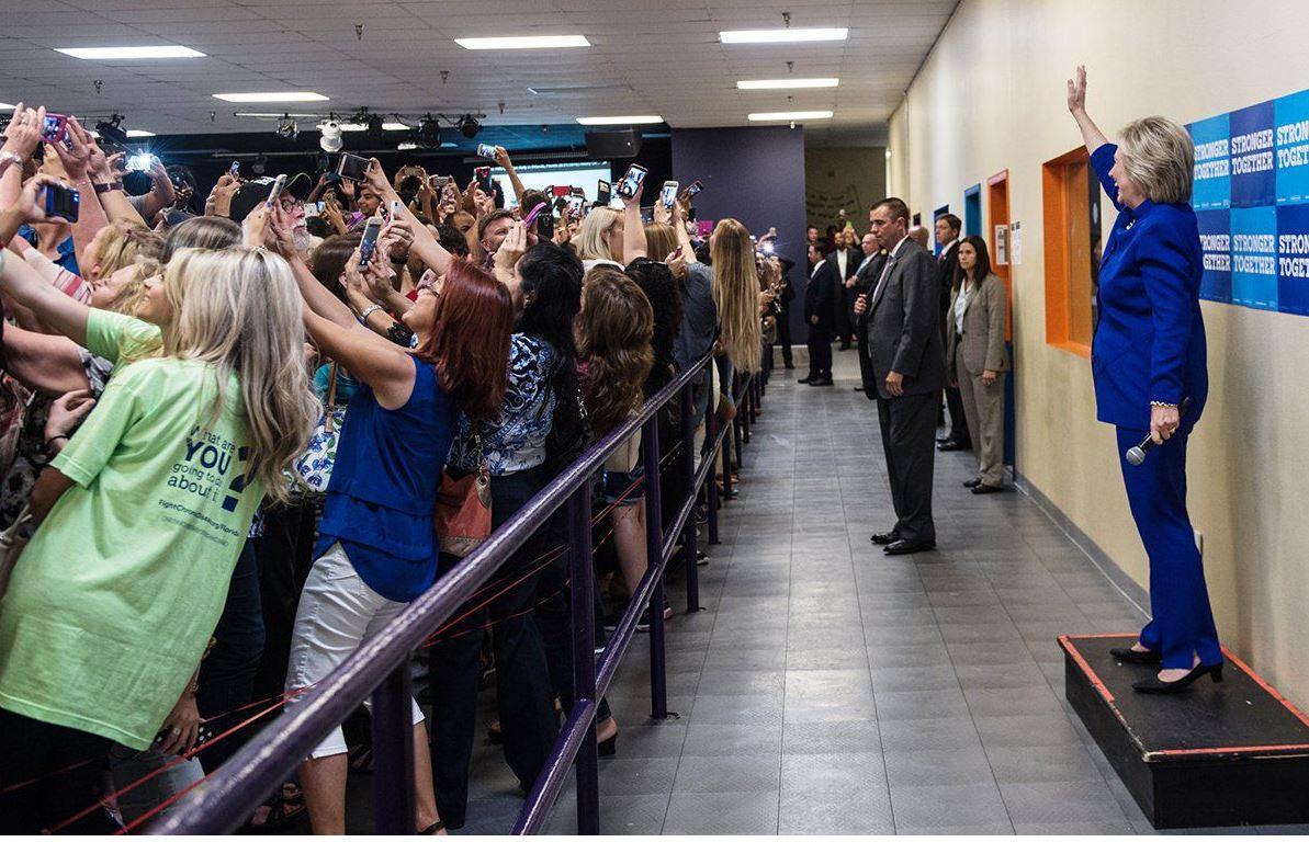 Plano general, color. Hillary Clinton pidiendo a su público que se haga selfies con ella de fondo.