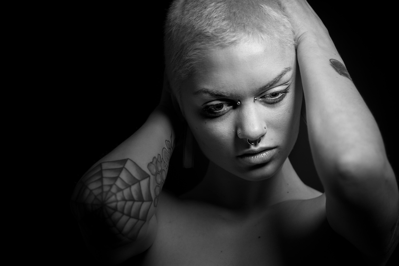 Plano medio, blanco y negro. Modelo con el pelo rapado y tatuaje de tela de araña en el codo.