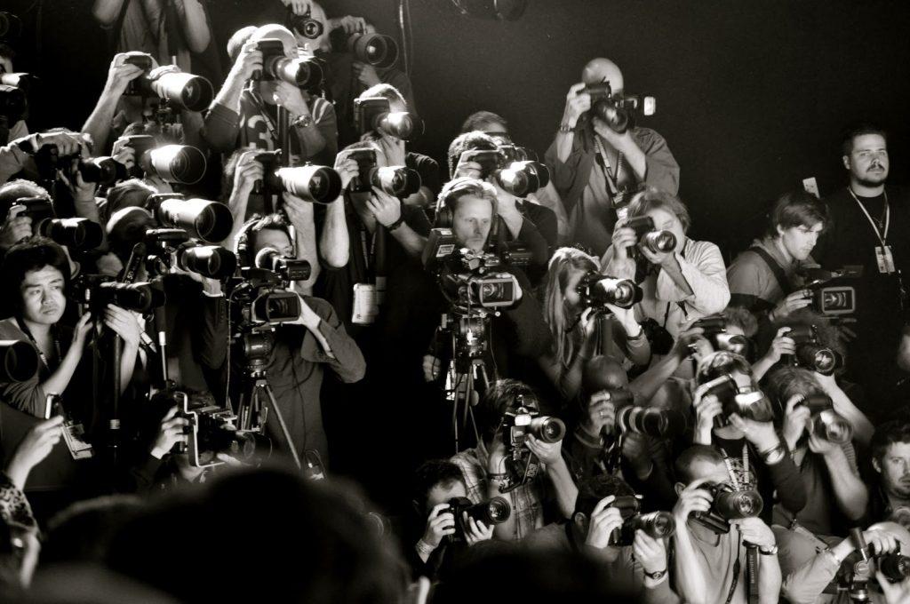 Plano general, blanco y negro. Multitud de fotógrafos al final de una pasarela de una semana de la moda disparando sus cámaras
