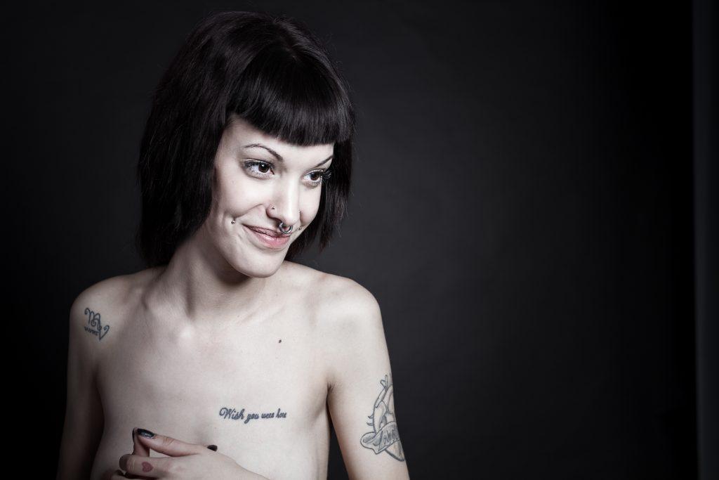 Plano medio, color. Modelo desnuda y tatuada de semiperfil sonriendo.