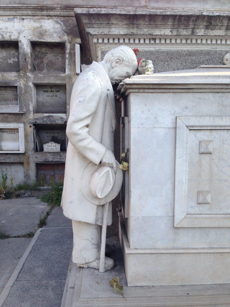 Plano general, color. Estatua de hombre inclinado, apesadumbrado, sobre tumba
