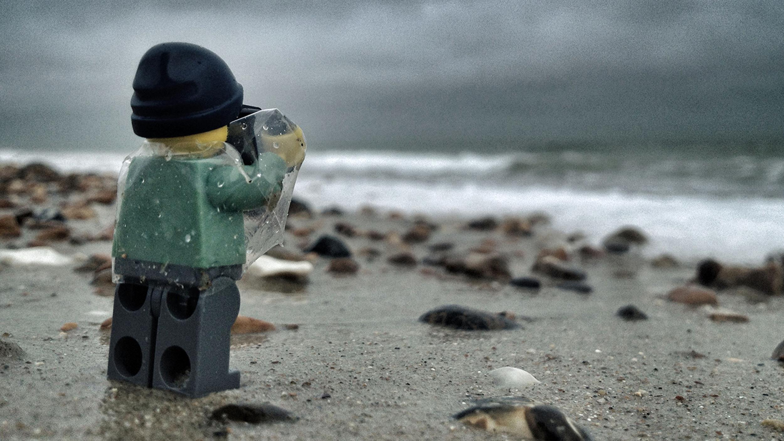 Muñeco Click de Playmobil con chubasquero haciendo foto en playa