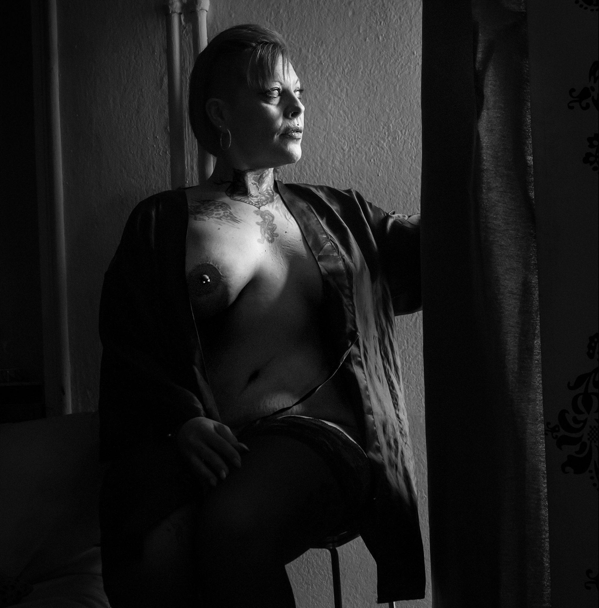 Mujer mayor tatuada y desnuda apartando cortina para mirar por la ventana