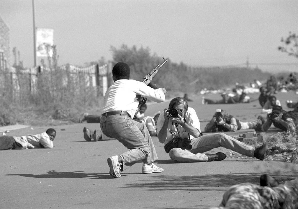Blanco y negro. James Natchwey fotografiando, sentado en el suelo, en medio de un combate.