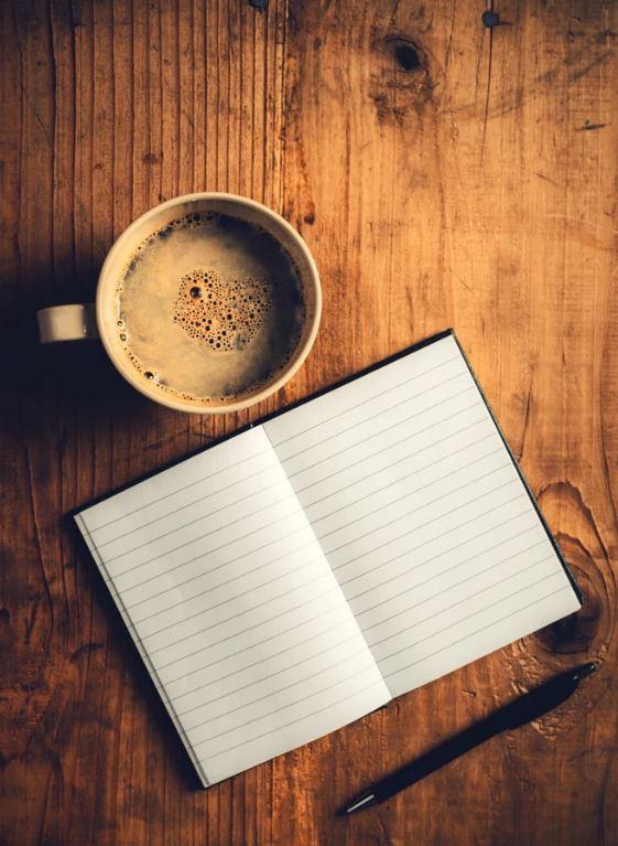 links imprescindibles 2018. Taza de café, bloc de notas y bolígrafo sobre mesa de madera rustica.