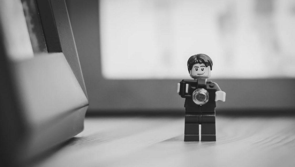 Fotógrafos mediocres. Muñeco de juguete (Click de Playmobil) sujetando una cámara fotográfica.