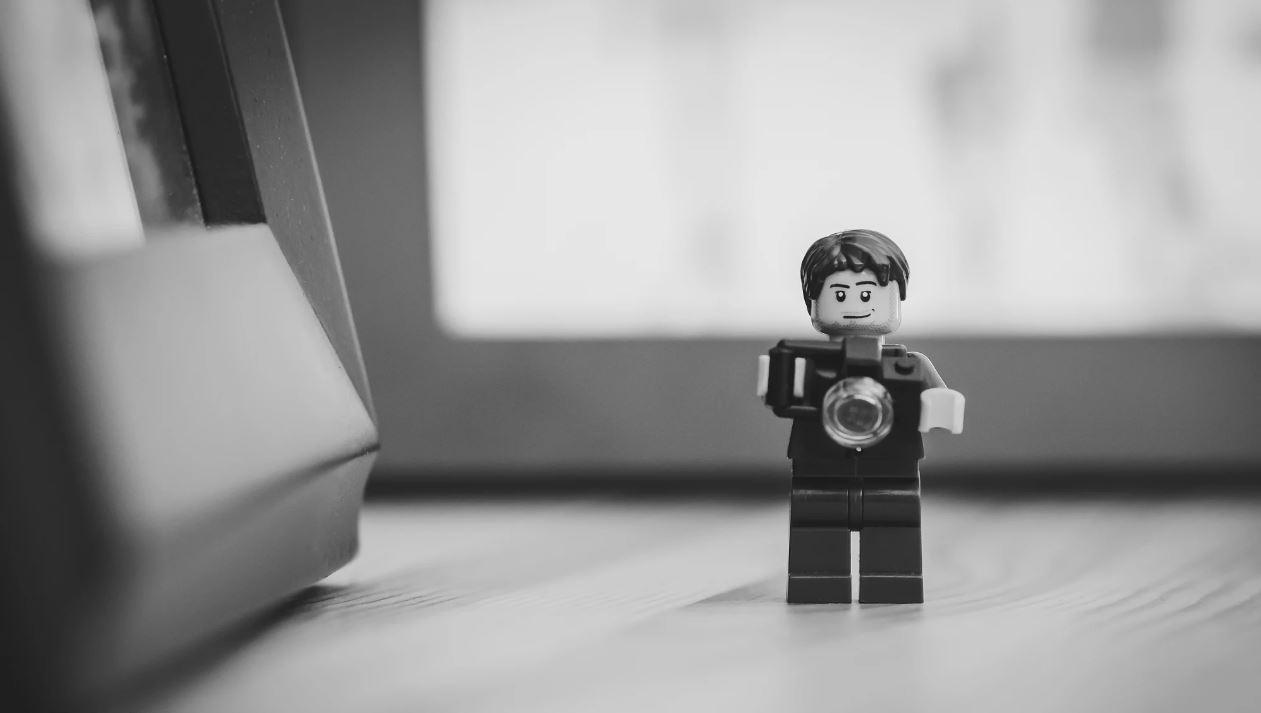 Muñeco de juguete (Click de Playmobil) sujetando una cámara fotográfica.