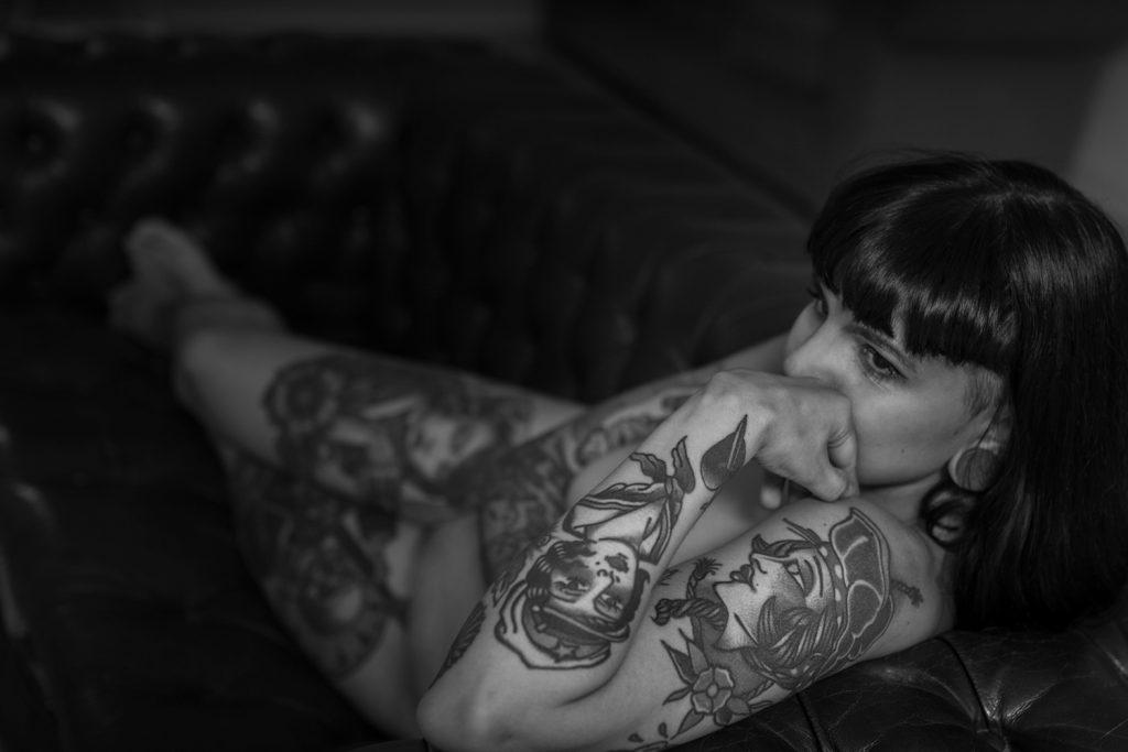 Blanco y negro, plano general. Modelo, tatuada y desnuda, recostada en un sofá en actitud pensativa.
