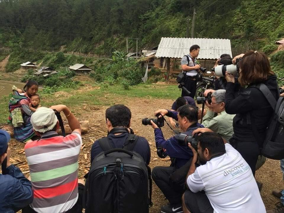 Plano general, color. Grupo de fotógrafos, Asia, rodeando mujer pobre con hijo.