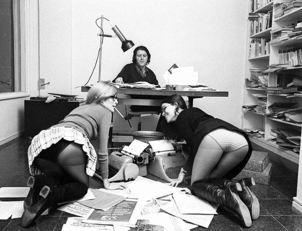 Libertad de expresión y censura. El editor Jorge Herralde, en los 70, sentado en la mesa de su despacho con sus secretarias de rodillas en el suelo. Sonriendo y enseñando las bragas.