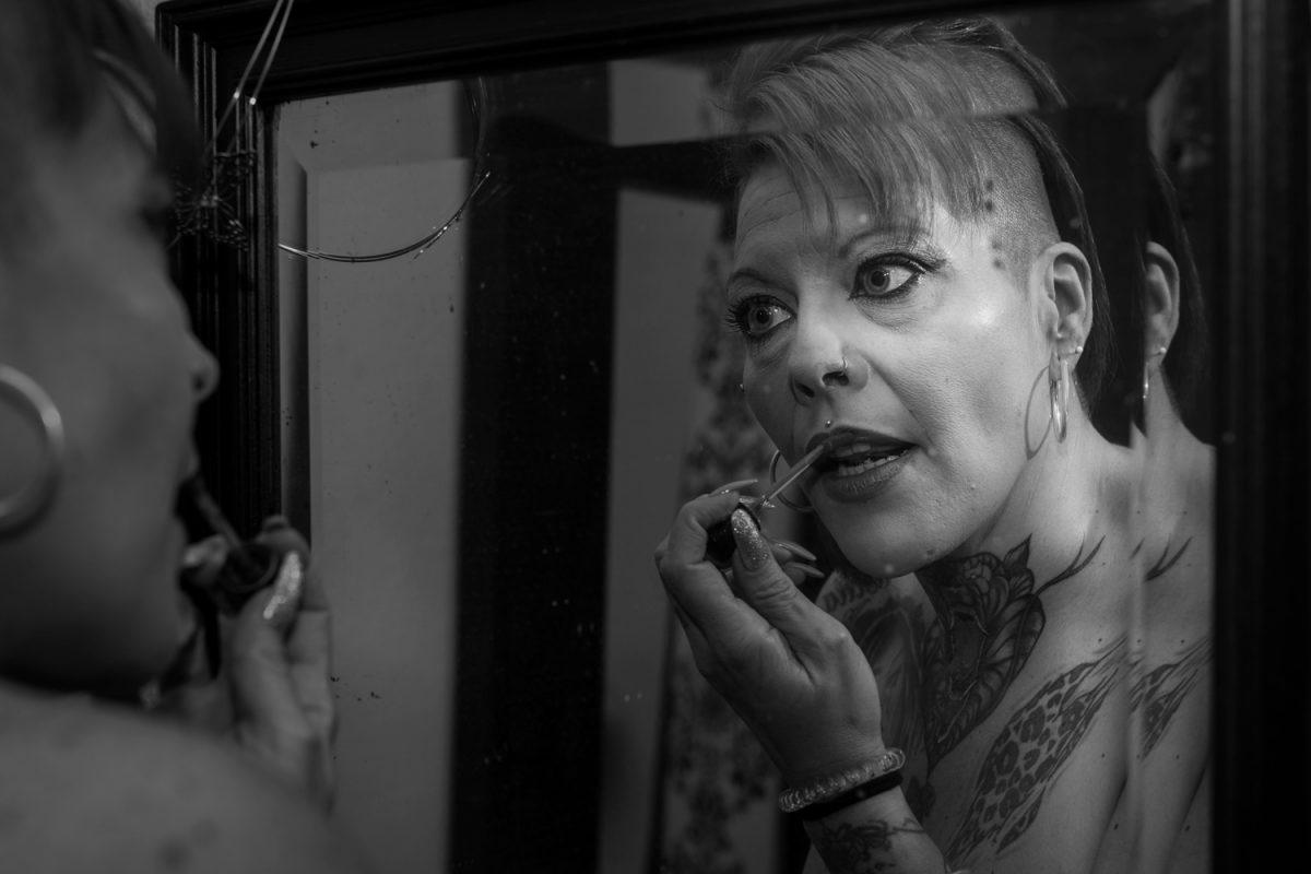 Primer plano, blanco y negro. Modelo tatuada y vieja, maquillándose delante de un espejo roto.
