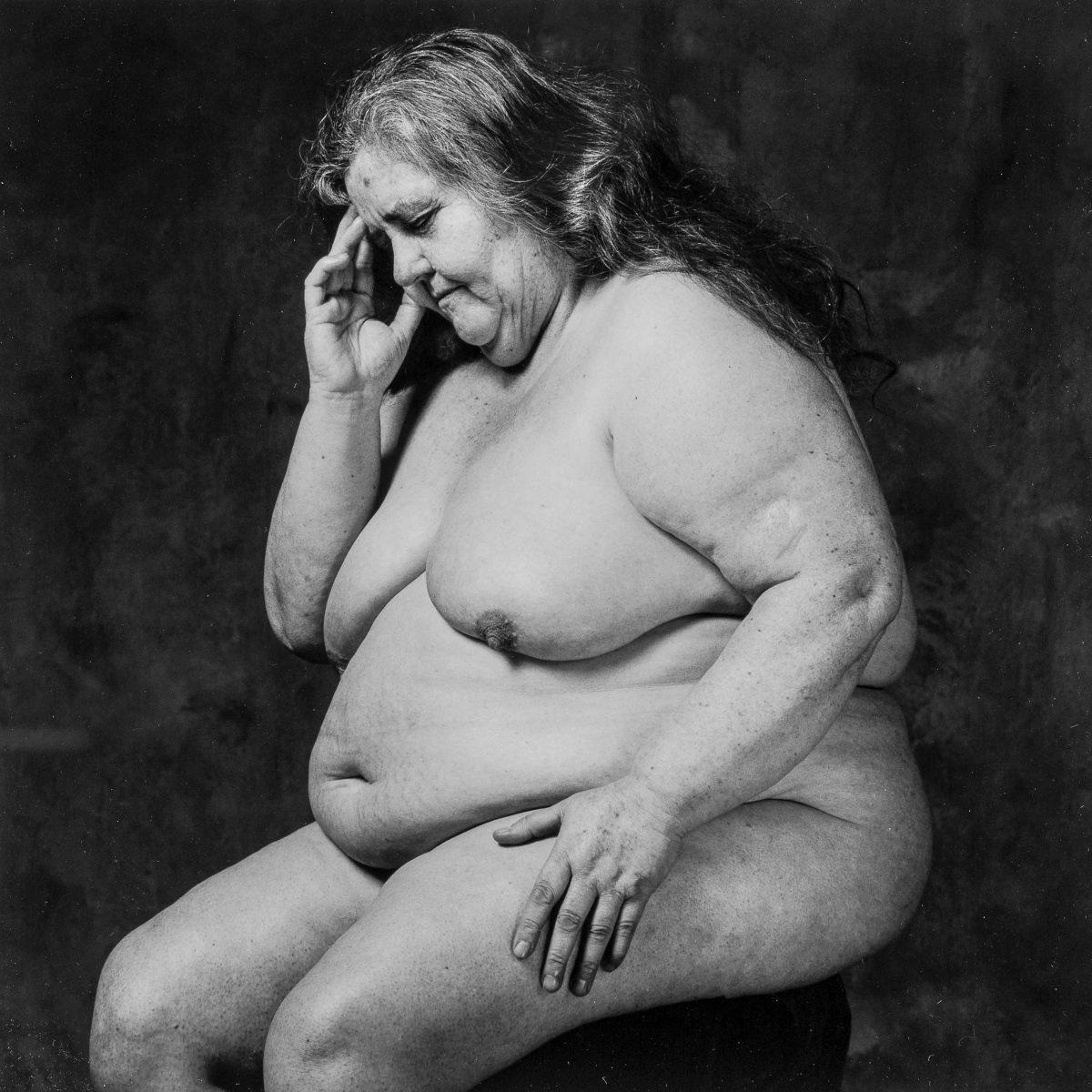 Plano americano, blanco y negro. Mujer desnuda, con sobrepeso mórbido, sentada en actitud que recuerda al pensador de Rodin.