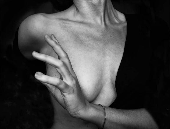 2020: fotografía, amigos y maestros. Imagen en blanco y negro. Mujer con el pecho descubierto. No se le ve la cara. La mano con un gesto tapa el pecho.