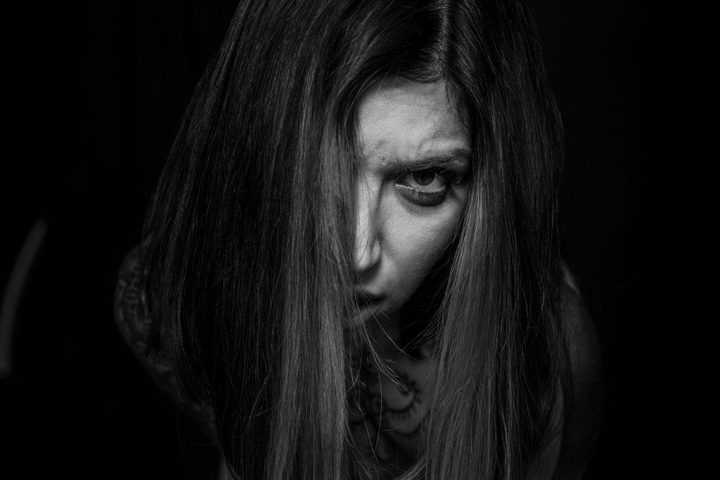 Hannie Masri. Retrato en blanco y negro. Primer plano. Pelo tapando la mitad del rostro. Mirada, enfadad, directa a cámara.