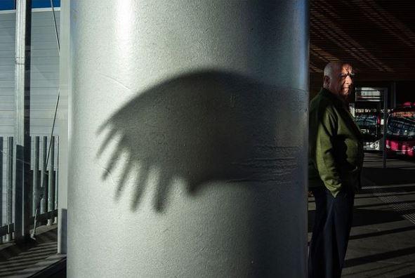 2020: fotografía, amigos y maestros. Imagen en color. Hombre junto a una columna en la que se ve la sombra de un ala.